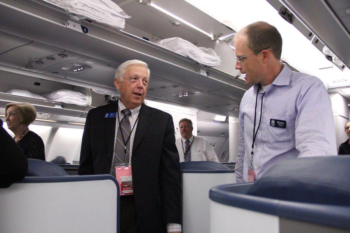 Former Tabernacle Choir President Ron Jarrett, left, converses with choir member Barry Hillam on jet airliner.