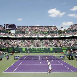 Novak Djokovic, foreground, of Serbia, serves to Andy Murray, of Great Britain, during the men's singles final match at the Sony Ericsson Open tennis tournament on Sunday, April 1, 2012, in Key Biscayne, Fla.