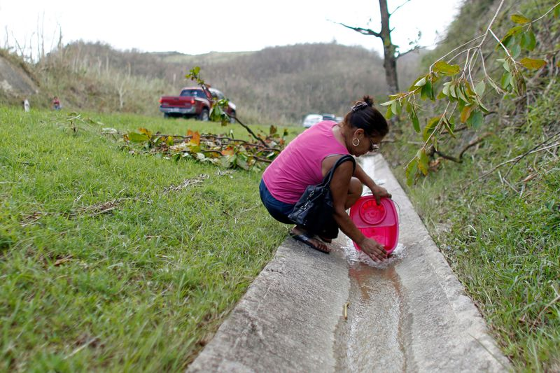 A Woman Collects Water From An Open Road Drainage Of A Natural Spring Created By The Landslides In A Mountain Next To A Road In Corozal Southwest Of San