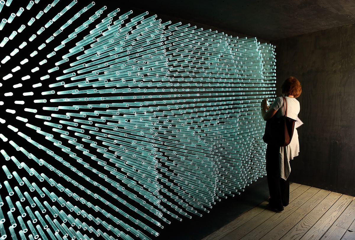 BERKELEY, CA - AUGUST 23: A U.C. Berkeley Botanical Gardens visitor looks at the art installation 'SOL Grotto' that was made by using glass tubes that were to be used by the now defunct solar company Solyndra on August 23, 2012 in Berkeley, California. Be