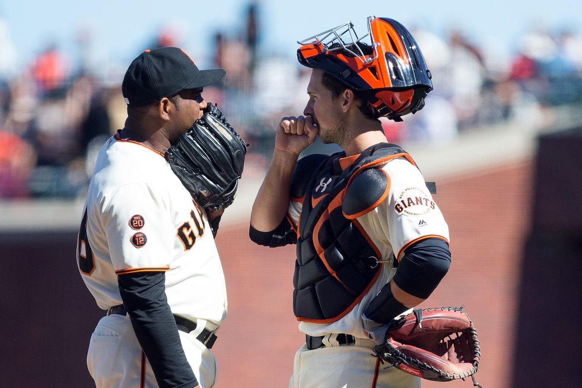 Buster Posey tries to fire a sunflower seed at Santiago Casilla's face. But Casilla is too quick with the glove hand block.