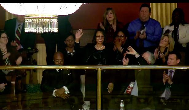 Detroit teacher Marla Williams waves during Michigan Gov. Gretchen Whitmer's State of the State address.