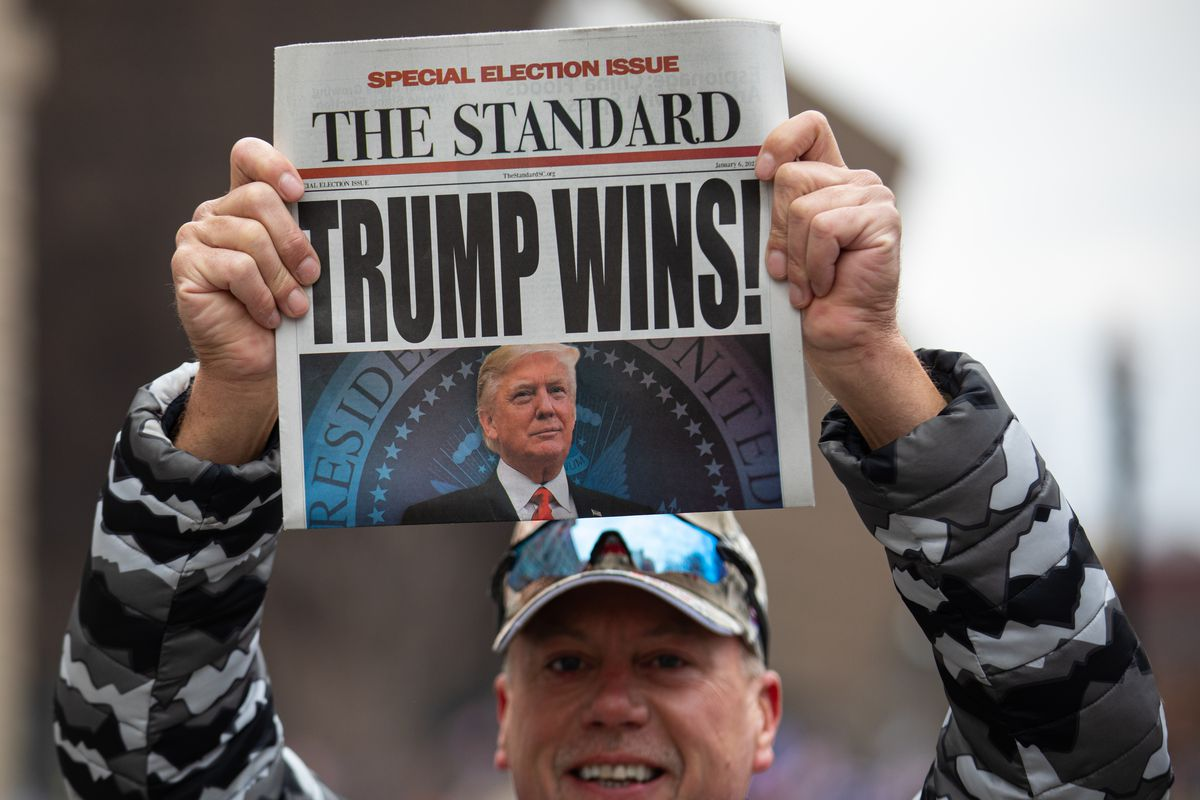 """A man holding a newspaper above his head that reads """"Trump Wins!"""""""