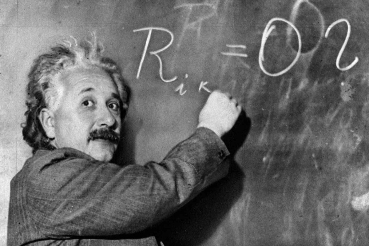 Black and white photo of Einstein at a chalkboard.