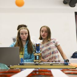 Thirteen-year-olds Jenna Eversole, right, and Tessa Eversole watch the table tennis ball they launched from a robotic launcher sail through the air during the University of Utah's annual Engineering Day event on campus in Salt Lake City, Saturday, Nov. 23, 2019. More than 600 students from around the nation registered for the annual event that gives parents and students an inside look into the different areas of engineering study offered at the university.
