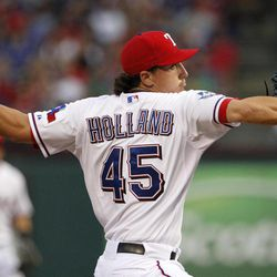 Texas Rangers' Derek Holland (45) delivers to the Chicago White Sox in the first inning of a baseball game on Saturday, April 7, 2012, in Arlington, Texas.