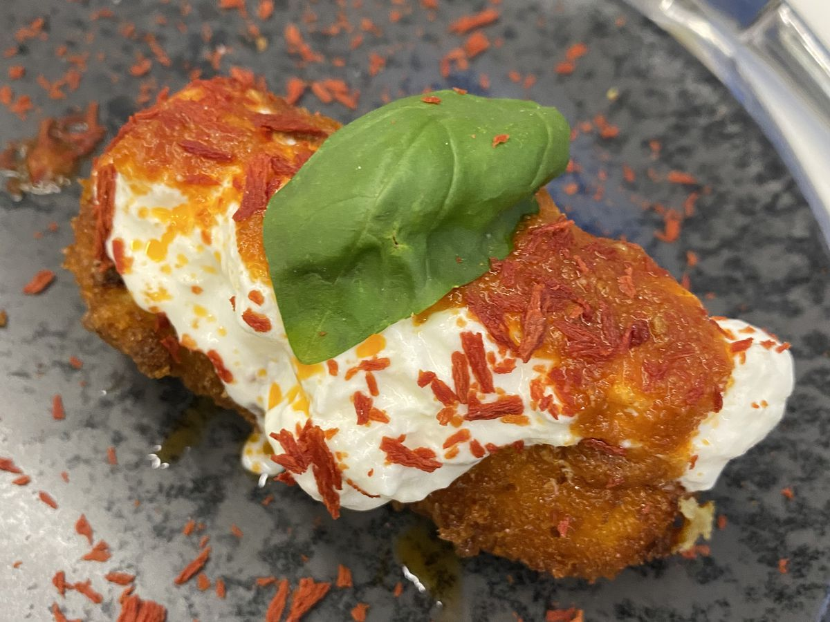 A croquette bursting with cheese and topped with pepper flakes and a leaf of basil