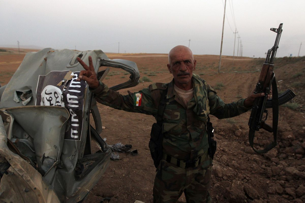 A Kurdish fighter poses next to a destroyed ISIS truck.