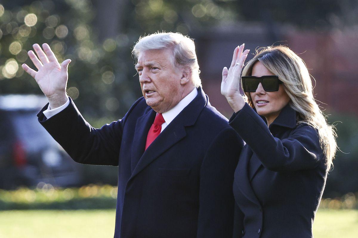 Donald Trump and Melania Trump walking and waving.
