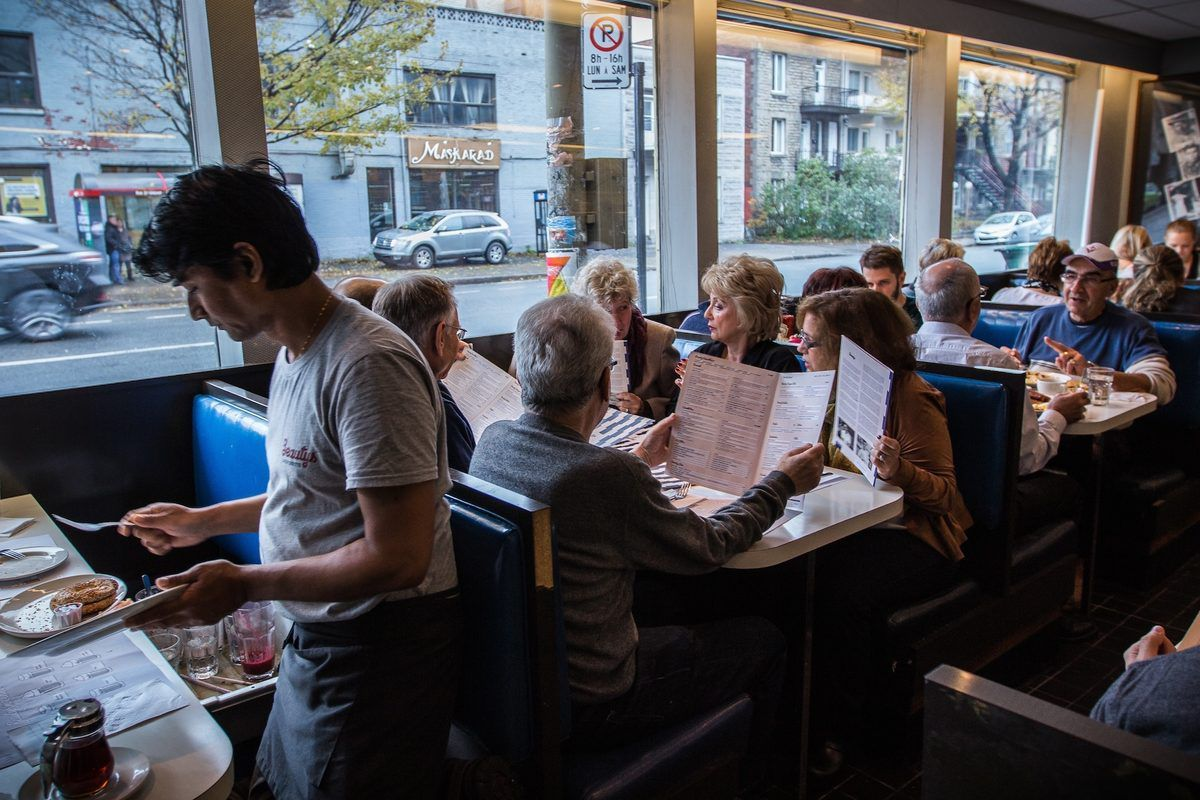 A group sits at a diner table next to a window while a server carries plates nearby.