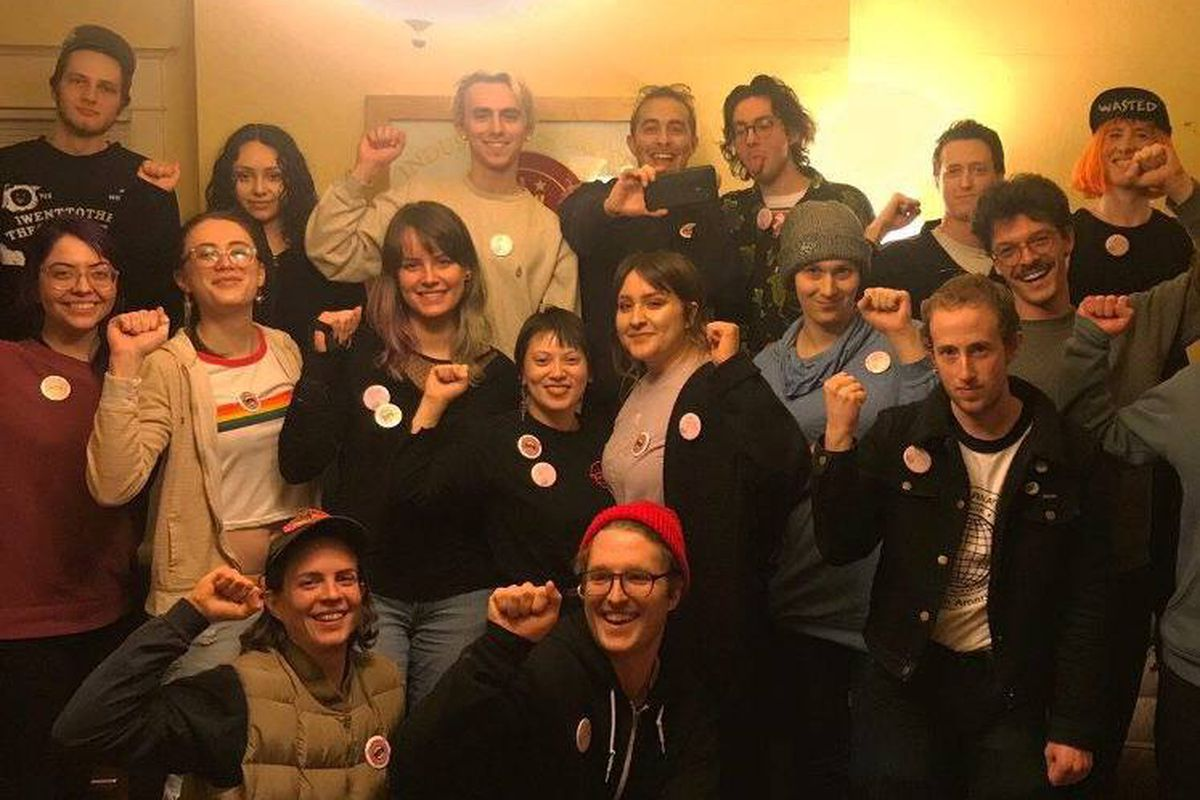 Little Big Burger employees stand together with solidarity fists. Most of them are wearing buttons for the union, standing inside a room with white walls.