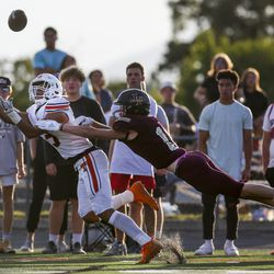 Timpview wide receiver Raider Damuni (3) reals in a ball while defended by Lone Peak defensive back Justin Ostler (11) during the first half of a high school football game at Lone Peak High School in Highland on Friday, Aug. 16, 2019.