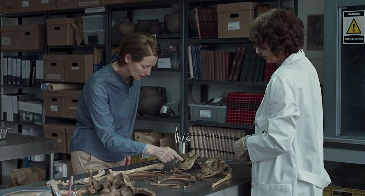 Tilda Swinton and a lab-coated character examine a pile of human bones in a room full of books and boxes in Memoria