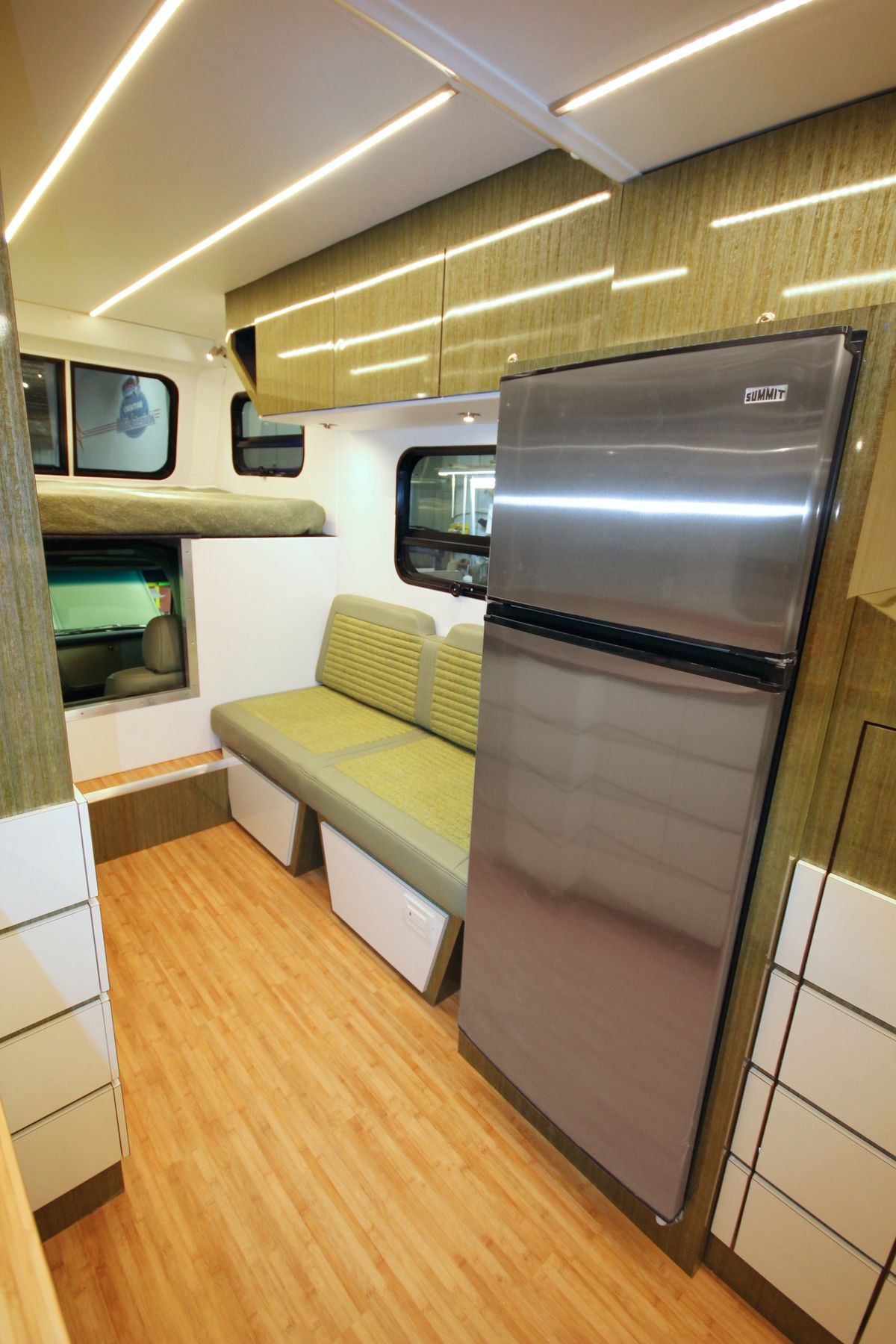 The camper has a full-size stainless steel fridge, wood floors, a green bench seat, and white cabinets.
