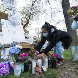 A woman from the Little Village community tend to the memorial for Adam Toledo, located near 24th St. and Sawyer Ave. Thursday, April 15, 2021 in Chicago. Adam Toledo, a 13-year-old Chicago boy appears to have dropped a handgun and begun raising his hands less than a second before a police officer shot and killed him last month, footage released Thursday under community pressure shows.