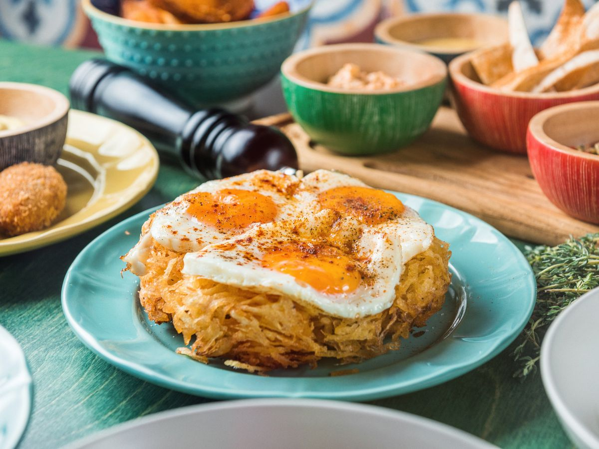 A large pile of baked potatoes beneath three spiced fried eggs, on a plate surrounded by other brunch dishes