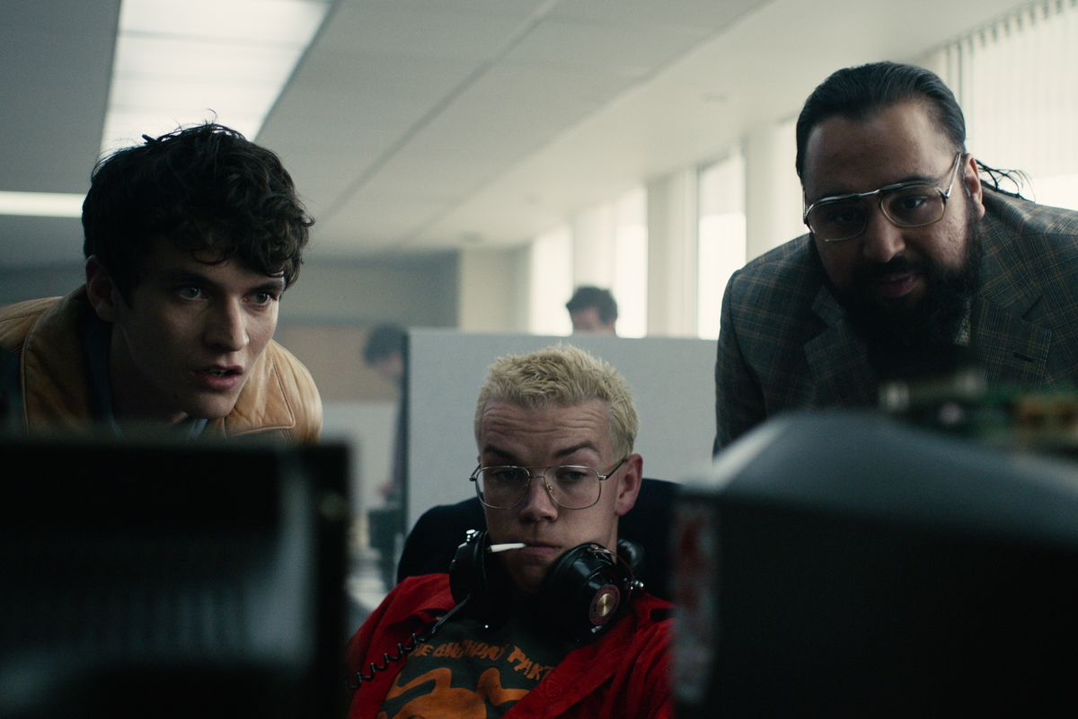 three men sit behind computer screeners watching a playthrough of the Bandersnatch video game