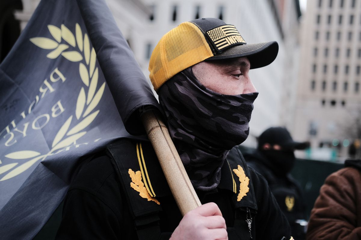 """A person carrying a """"Proud Boys"""" flag on their shoulder."""