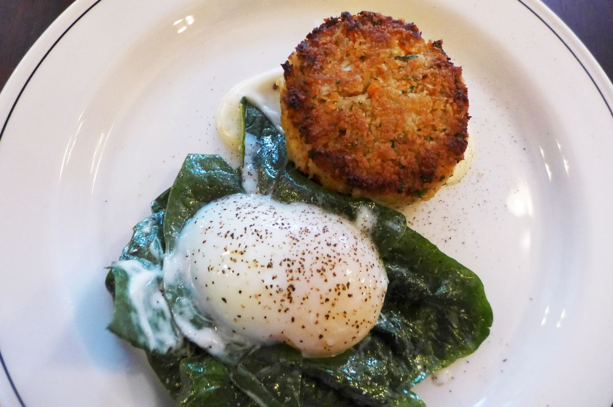 A plate with a puck shaped crab cake, undercooked egg, and spinach.