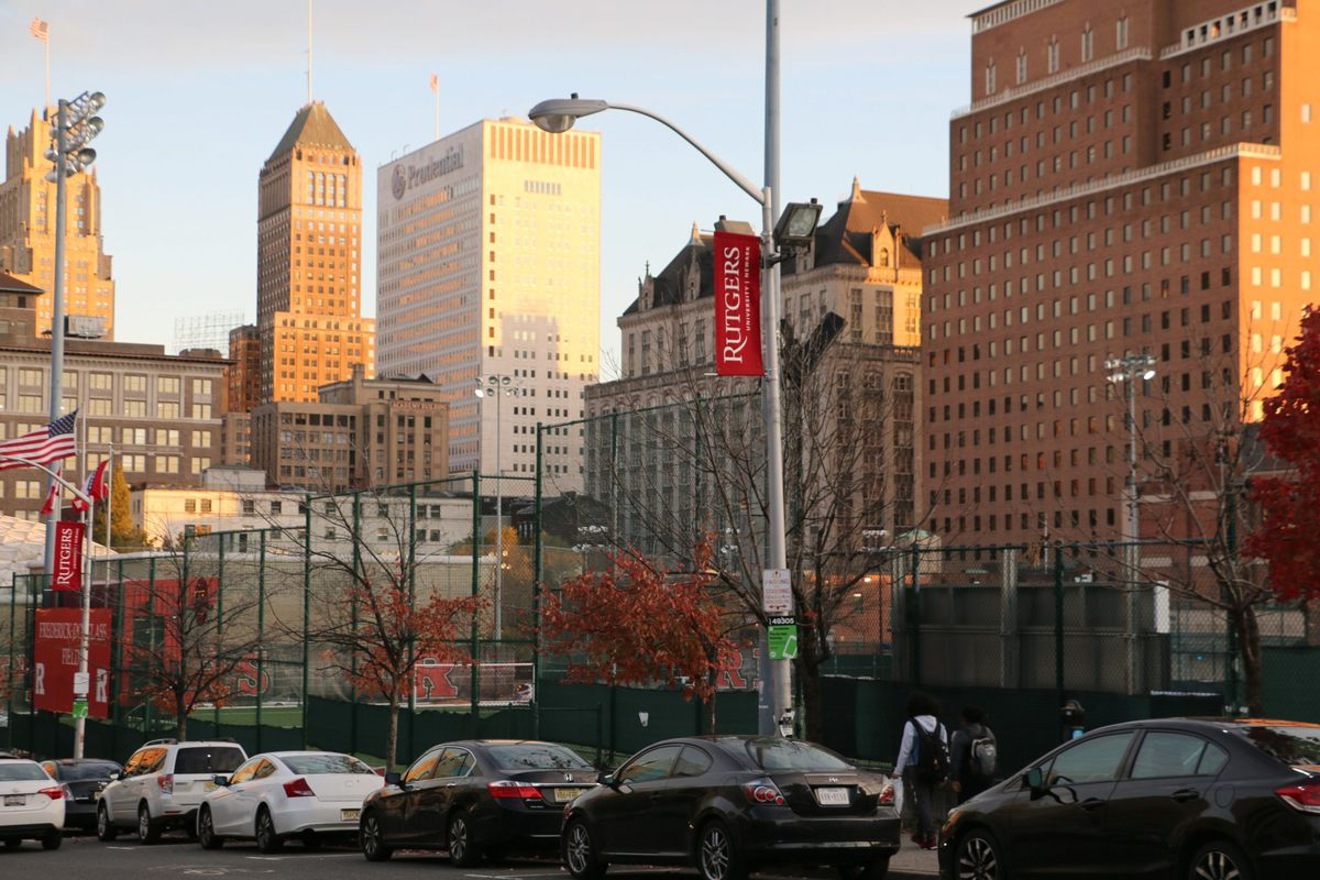 A photograph of the Newark campus of Rutgers University, with golden light reflecting against large buildings in the background.