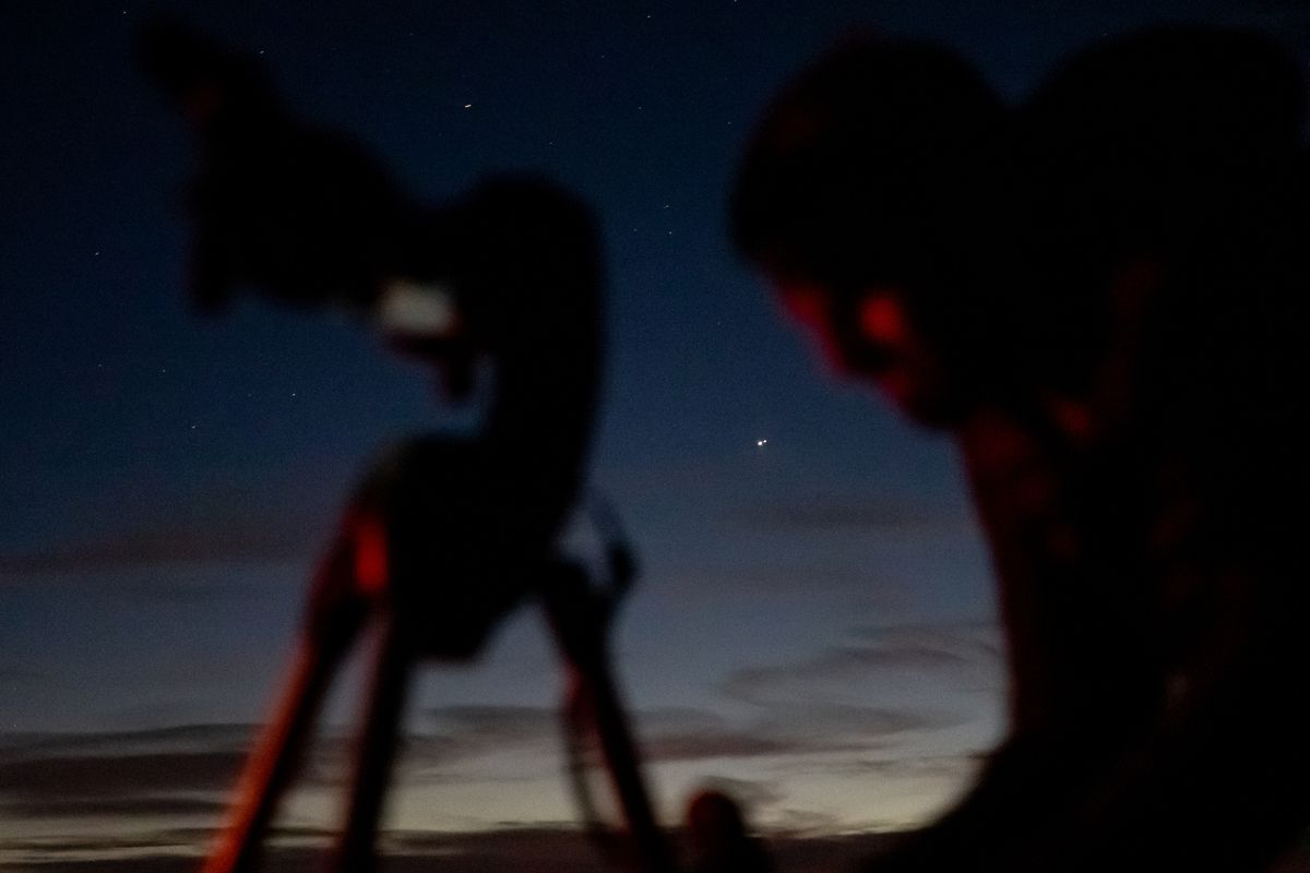 """Thom Allen prepares a telescope to view the """"Great Conjunction"""" of Saturn and Jupiter, visible in the center of the image, in the West Desert on Monday, Dec. 21, 2020. Also dubbed the Christmas Star, the conjunction is the closest together the two planets have passed in Earth's sky in nearly 400 years."""