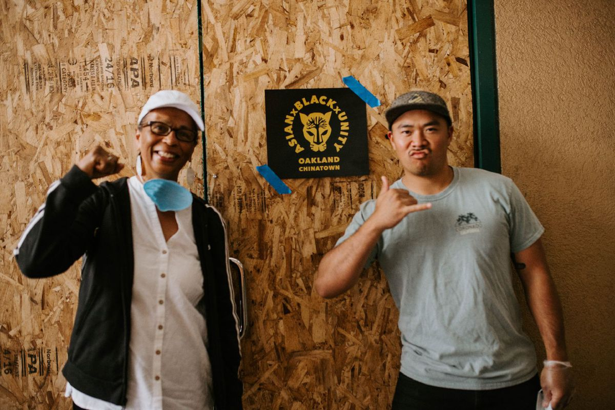 """Tarika Lewis (left) and Josh Felise, one of the Good Good Eatz volunteers standing in front of a """"Asian x Black x Unity"""" poster that Lewis designed"""