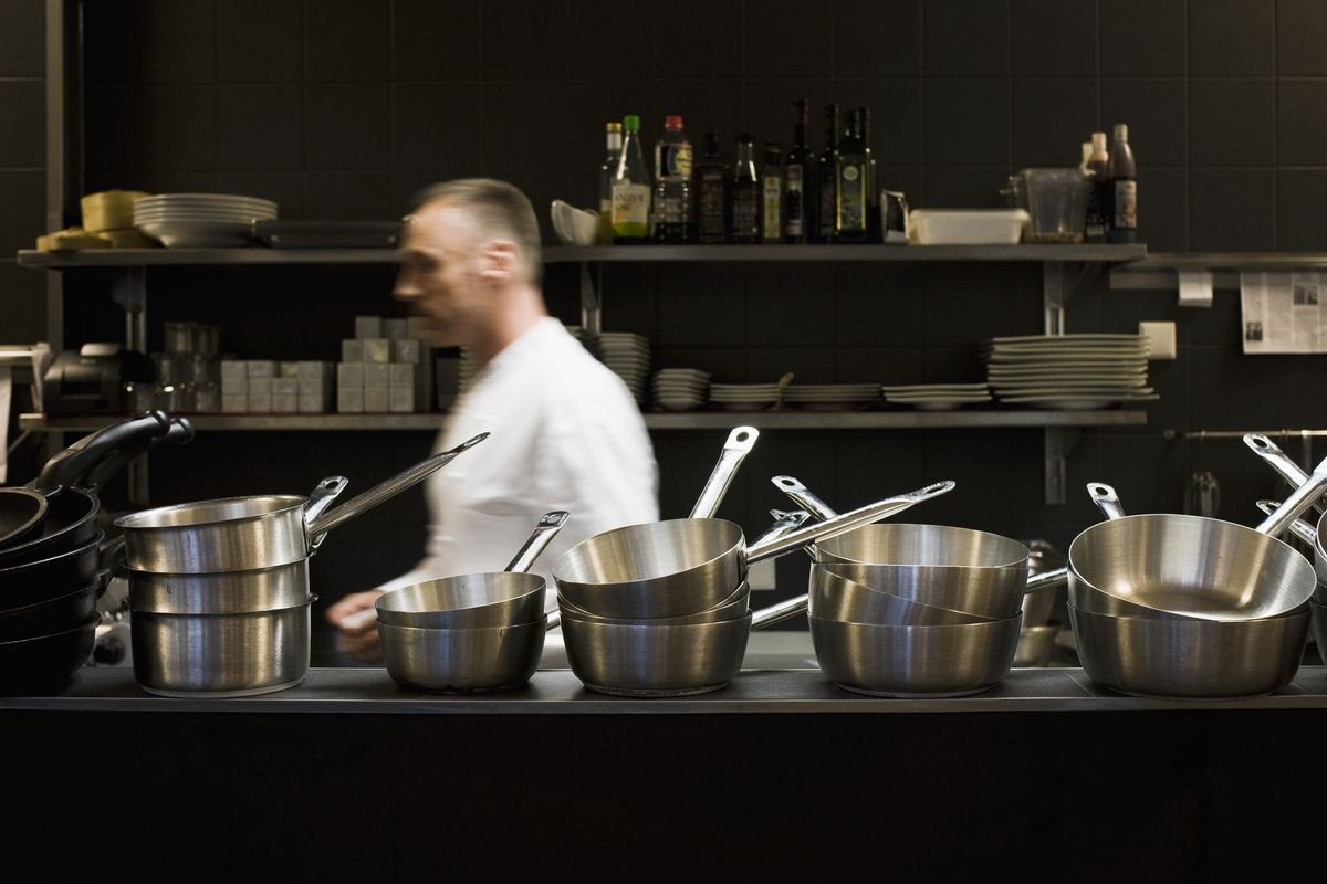 Stock photograph of a male chef in a restaurant kitchen, walking behind shelves full of silver pots and pans