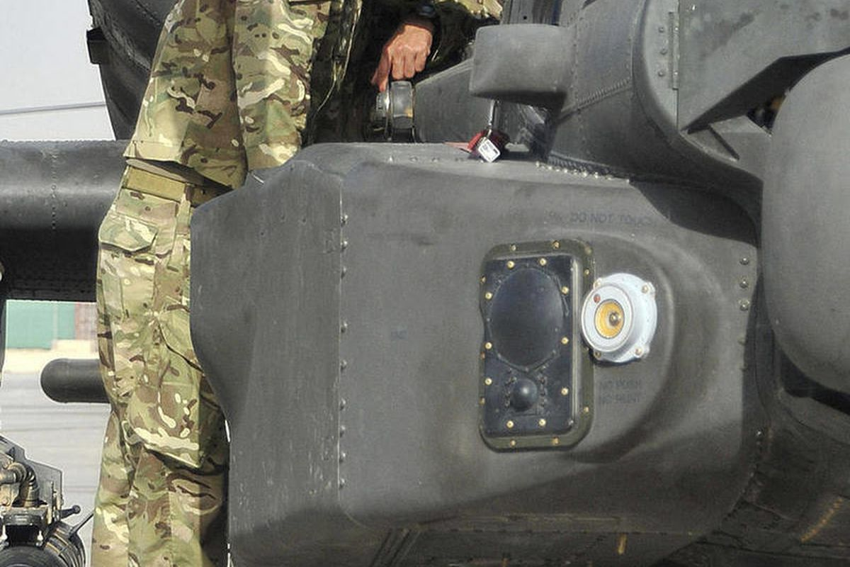 Britain's Prince Harry is shown an Apache helicopter by a member of his squadron, obscured behind, (name not provided) at Camp Bastion in Afghanistan, Friday Sept. 7, 2012.  Prince Harry, known to the military as Capt. Harry Wales, will be based at Camp B