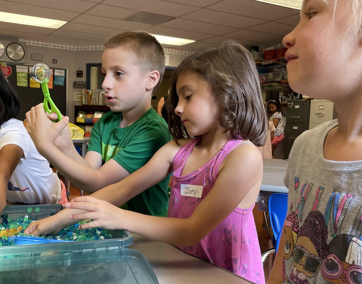 Young children play with blue gel beads during a summer program at their elementary school.