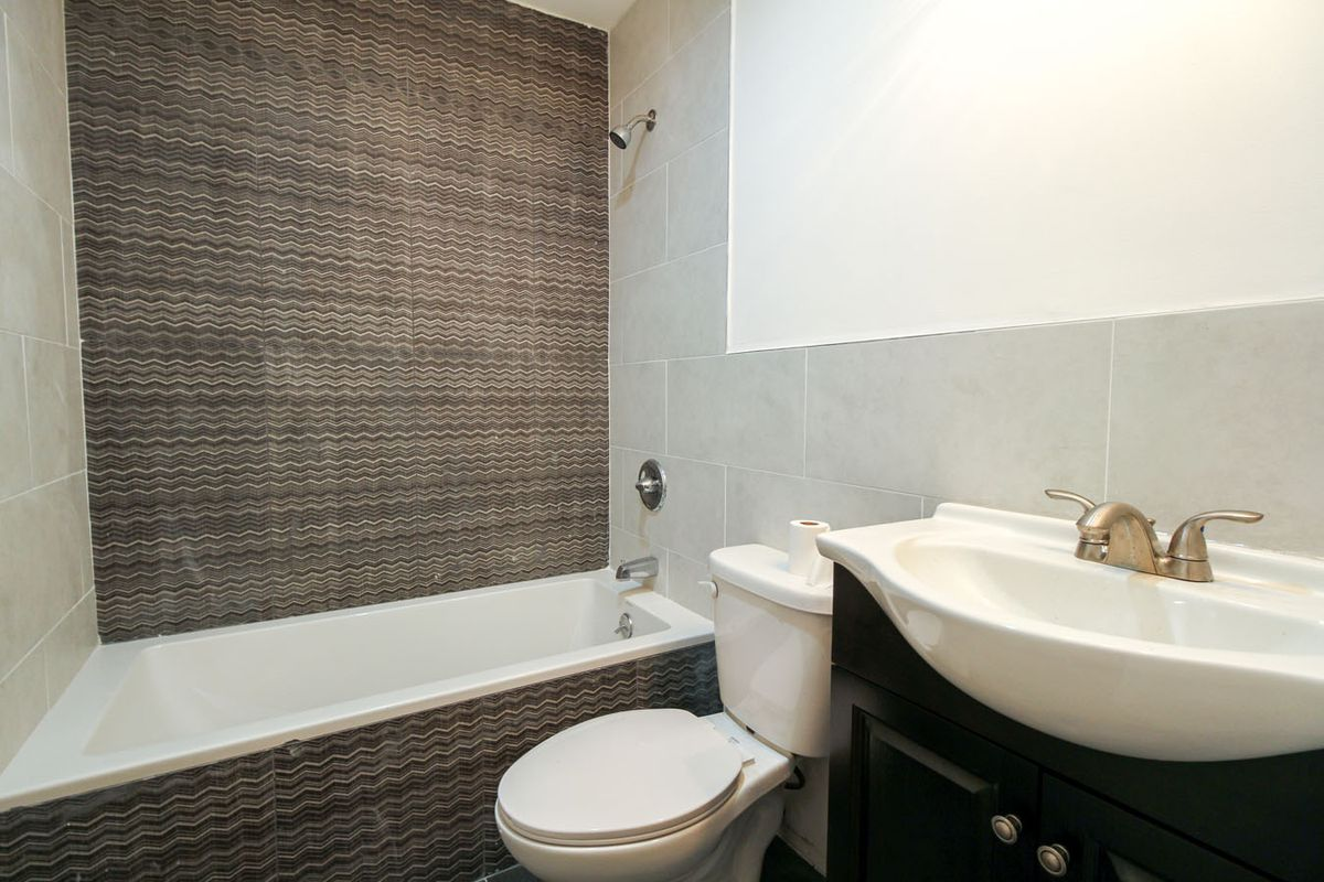 A bathroom with grey and brown tiles.