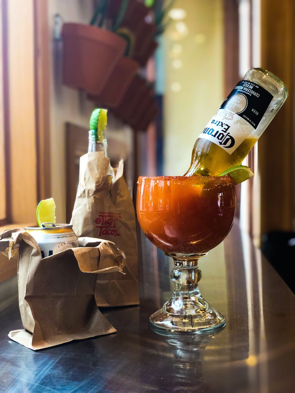 A picture of a michelada and two beers at Tight Tacos, which arrive in a margarita glass and paper bags, respectively