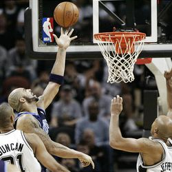 Utah Jazz player Carlos Boozer, center, scores between San Antonio Spurs defenders Tim Duncan, left, and Richard Jefferson during the second half of an NBA basketball game in San Antonio on Thursday. The Jazz had their first win in 10 years against the Spurs in San Antonio with a score of 90-83.