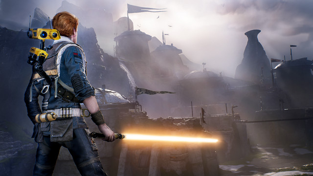 Cal Kestis brandishing an orange lightsaber with several mysterious buildings in a hazy background