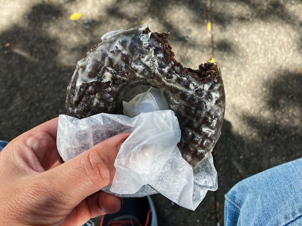 A hand holds a chocolate glazed doughnut with a bite taken out of it. The doughnut is partially wrapped in white tissue paper and is held over a sun-dappled sidewalk.