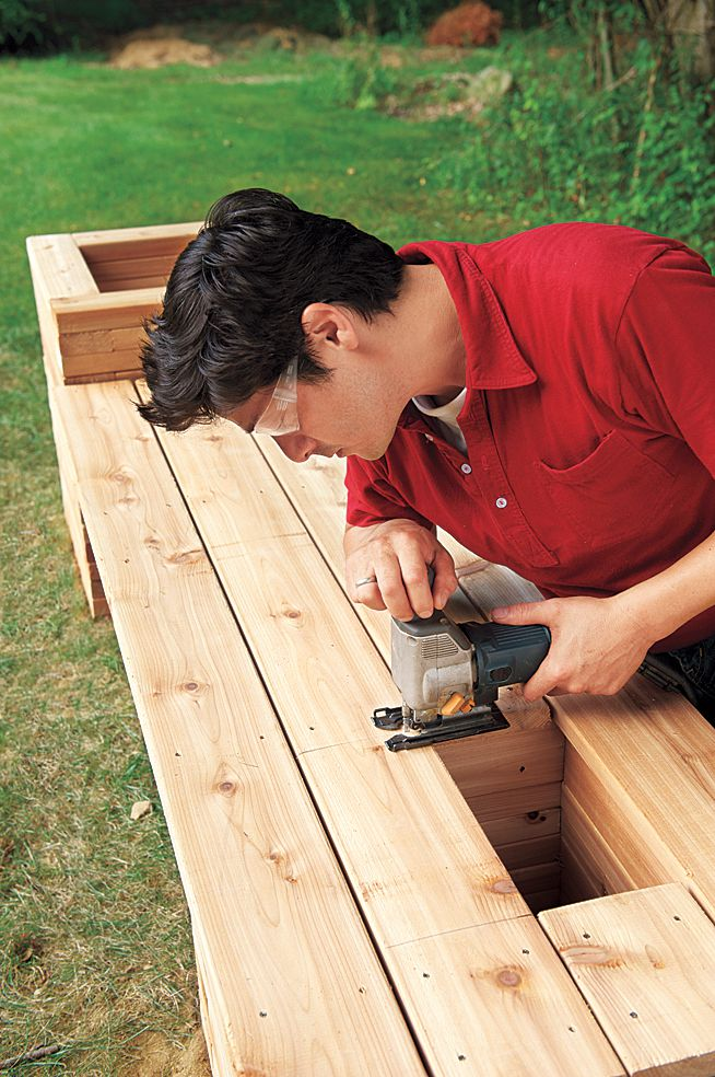 Man Cuts Planter Opening Into Seat Boards With Jigsaw Blade