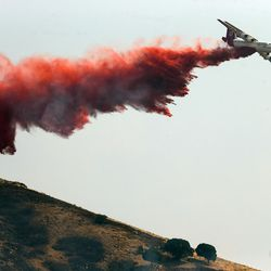 A heavy tanker drops retardant up on the mountain as fire burns homes and property near Weber Canyon on Tuesday, Sept. 5, 2017.