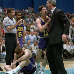 Jerry Sloan is restrained by John Stockton while Tom Chambers sits dejected on the floor after being ejected from Game 2 in a series against the Spurs.