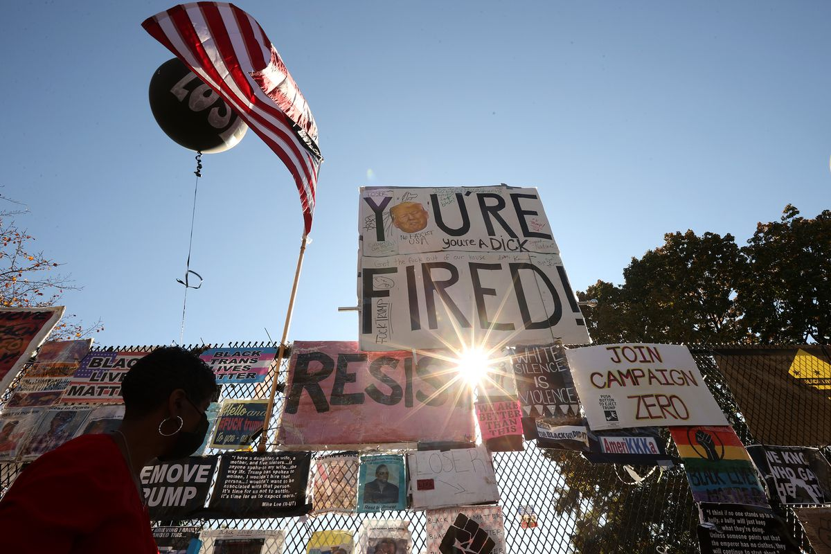 """Signs reading """"you're fired"""" and other anti-Trump slogans, along with an American flag."""