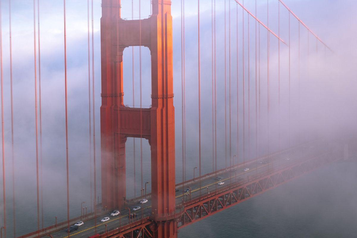 A tower of the Golden Gate Bridge, shrouded in fog.