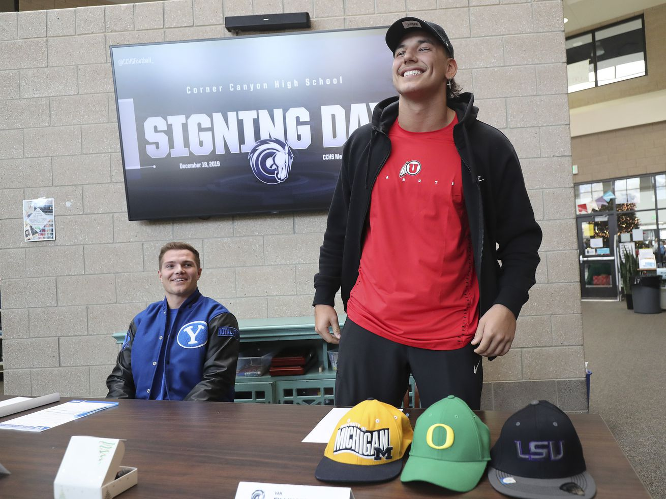 Corner Canyon High School athletes Van Fillinger, right, and Josh Wilson smile as they sign their National Letters of Intent in Draper, Utah, on Wednesday, Dec. 18, 2019. Fillinger signed with Utah and Wilson signed with BYU.