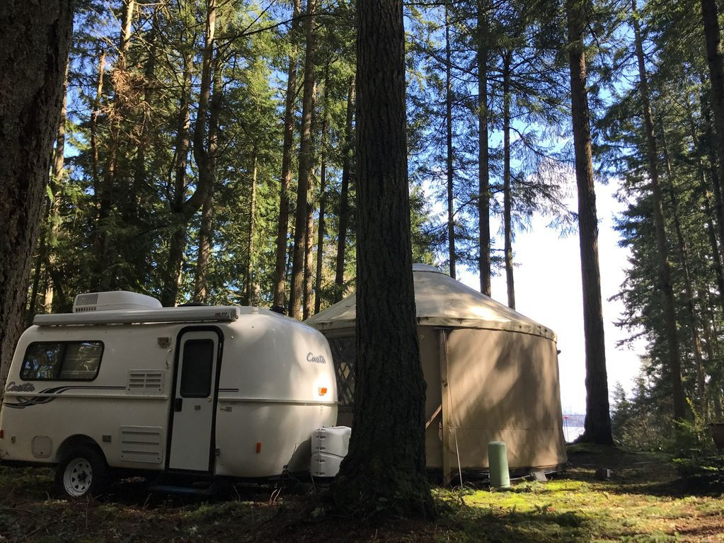 Among evergreen trees, a white, rounded trailer is parked in front of a beige yurt.