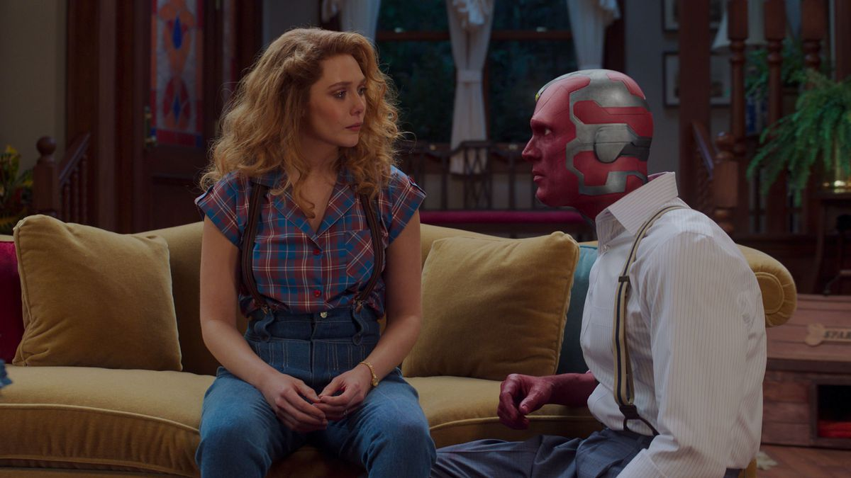 Wanda and Vision sit tensely on their couch in WandaVision.