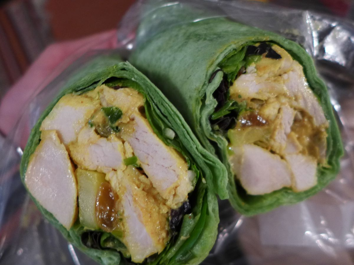 Seen in cross section a wrap with a green wrapper and a chicken salad inside.