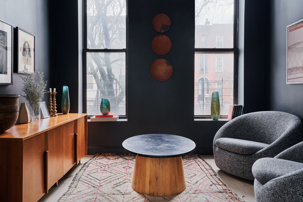 A living area with two large windows, dark blue walls, a round coffee table, and two grey chairs.