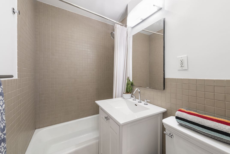 A bathroom with light brown tiles.