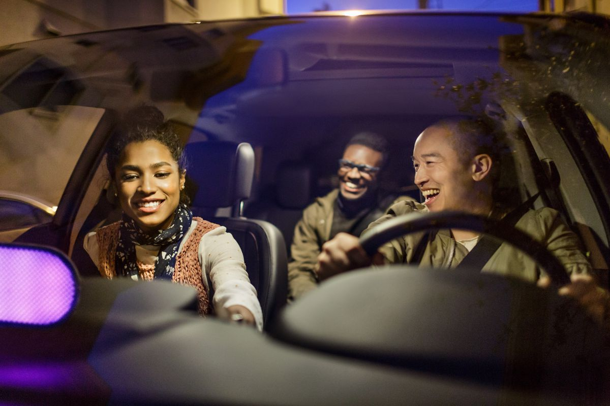 A Lyft driver takes two passengers to their destination.