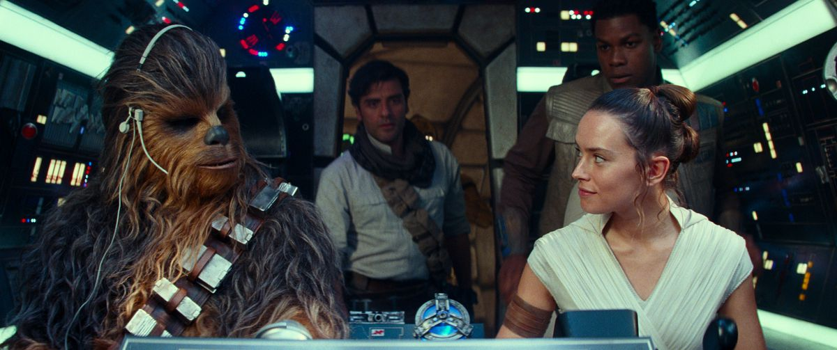 Star Wars: The Rise of Skywalker characters Chewbacca, Poe, Rey, and Finn look at each other in the Millennium Falcon.
