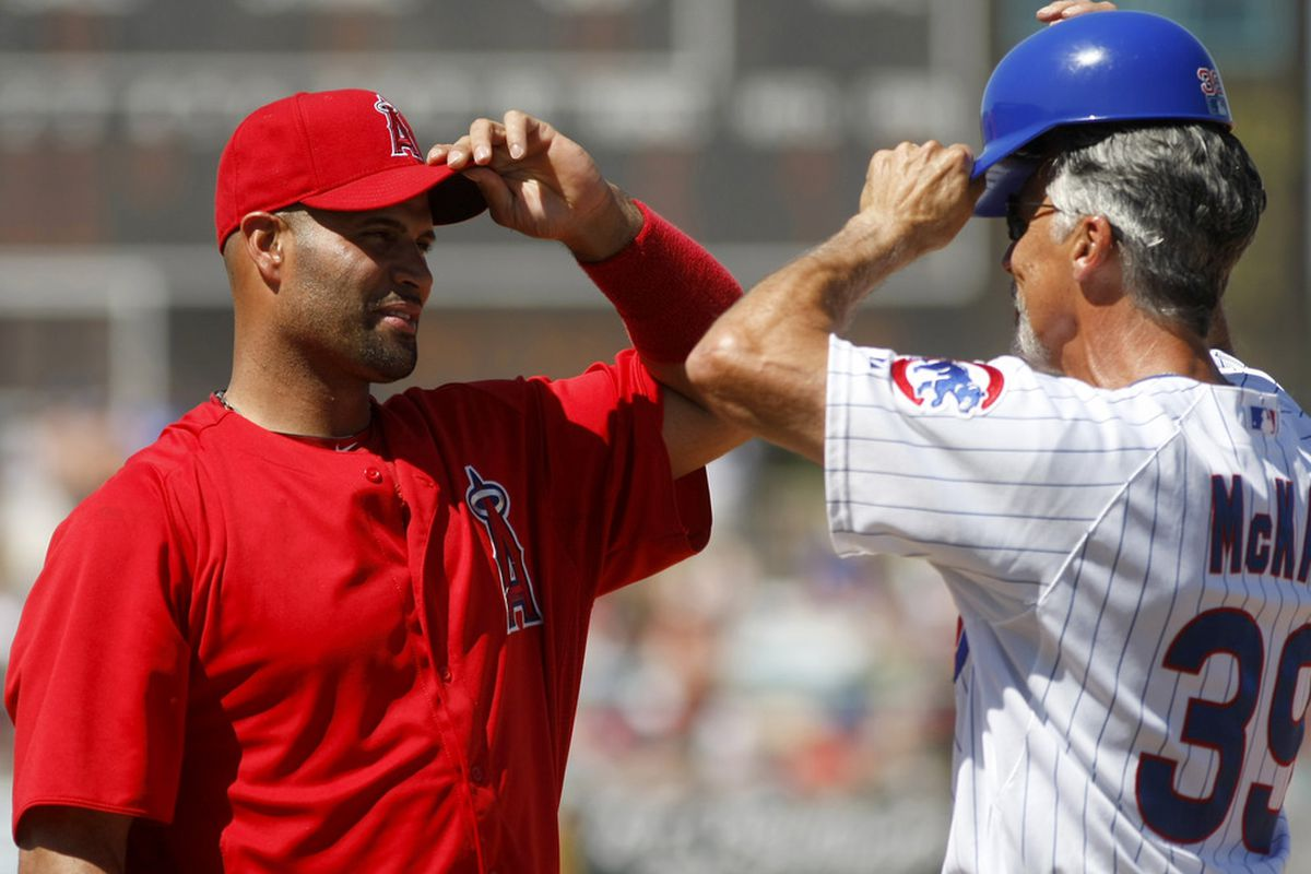 Former Cardinals salute: Mesa, AZ, USA; Los Angeles Angels first baseman Albert Pujols talks with Chicago Cubs first base coach Dave McKay in the first inning at HoHoKam Stadium.  Credit: Rick Scuteri-US PRESSWIRE
