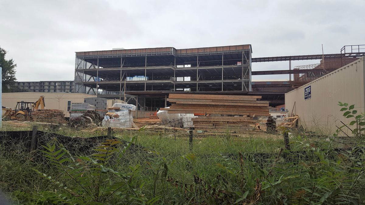 A steel frame of a building stands over lumber and construction vehicles.