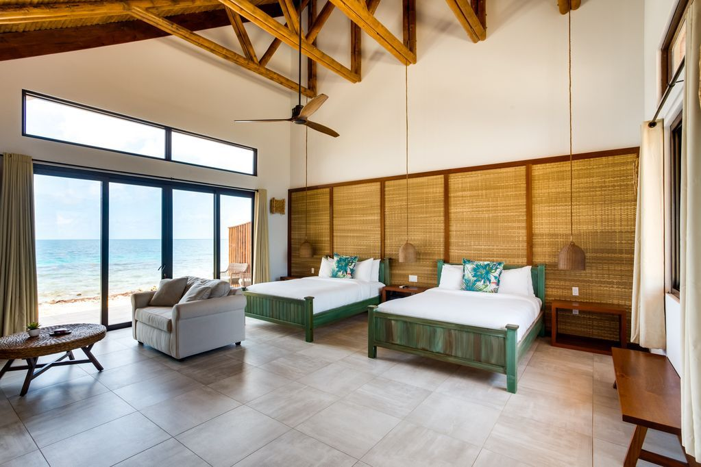 A bedroom with two beds against a backdrop of bamboo mats. There is a ceiling fan, armchair, and sliding glass doors leading to the shore.